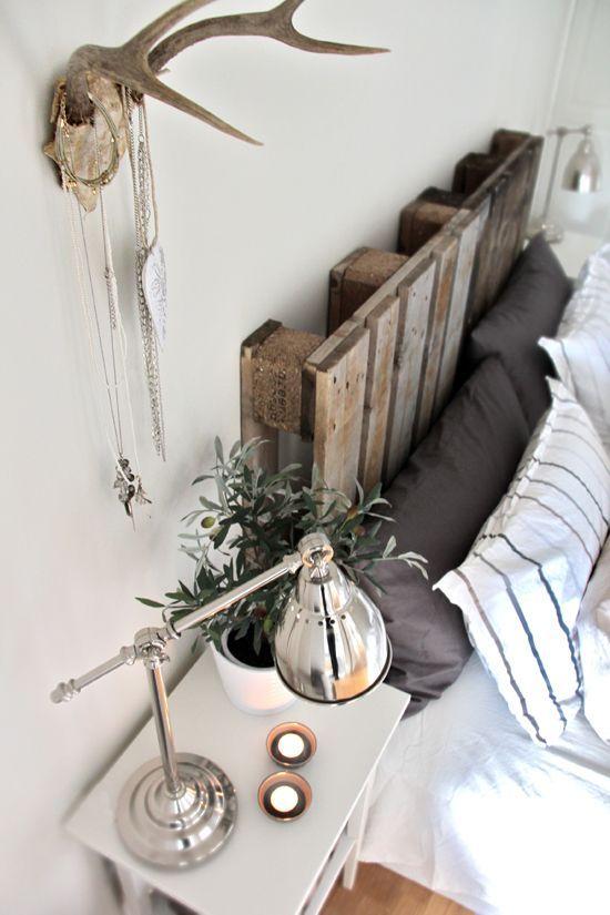Des palettes de bois en guise de tête de lit dans la chambre à coucher.