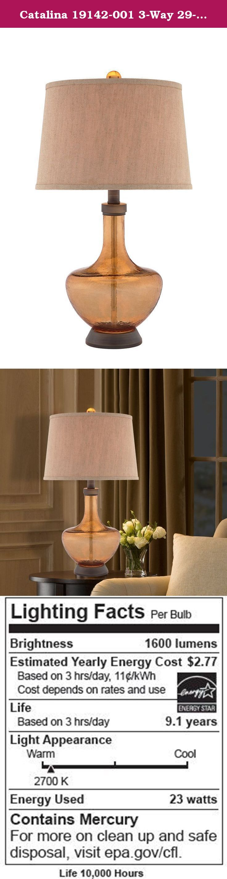 Catalina 19142-001 3-Way 29-Inch Amber Glass Table Lamp with Textured Linen Hardback Shade, Bulb Included. The Catalina 19142-001 3-Way Table Lamp offers a stylish transitional design. The glass table lamp features an amber glass base with metal accents in a dark bronze finish and textured linen hardback shade. This lamp is rated for 120-volts and uses a 3-way 150-watt incandescent bulb or 3-way E26 CFL spiral bulb. A 3-way E26 CFL spiral bulb is included. The light source is soft and the...