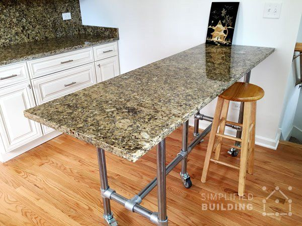 the table features a granite table top that matches the kitchen cabinet  counter tops perfectly.