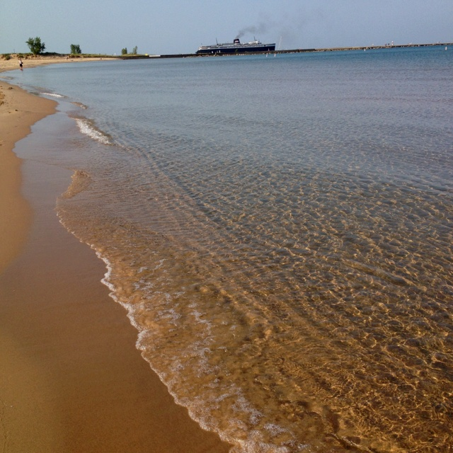 Stearns Park Beach with the S.S. Badger Ferry in the distance in Ludington, Michigan