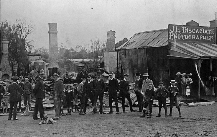 The remains of three shops in Scott Street, Warracknabeal, destroyed by fire early in the morning of Monday 22 August 1910. The buildings reported destroyed were the grocery section of G. Phillips store (a brick wall & iron door protected the drapery department), Lawson's bakery & confectionery establishment & Discaciatis Photographic Studio, though the front section is still standing on the right. Wollard's fruit shop was partly damaged by fire & water.