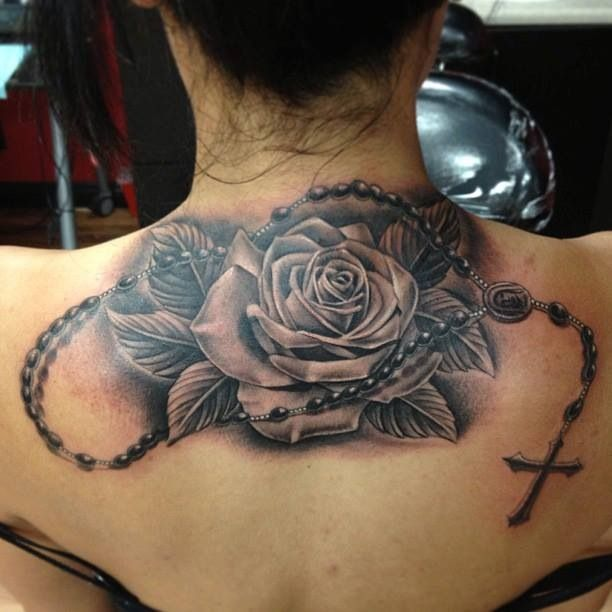 Female back rose and rosary tattoo