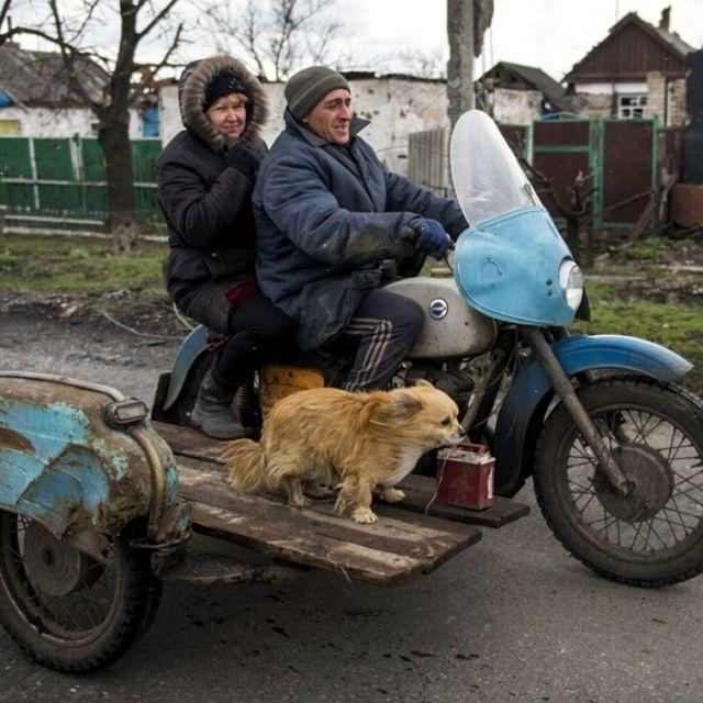Una coppia con cane a bordo di una moto con sidecar, nel villaggio di Nikishino, nell'autoproclamata Repubblica Popolare di #Donetsk, in #Ucraina
