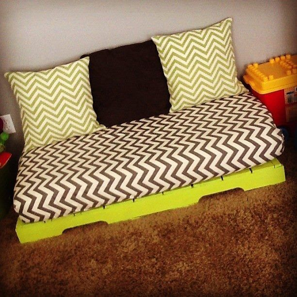 I made this for the boys' playroom. Get a pallet and paint it.  Find a crib mattress. Use your favorite fitted crib sheet tutorial, make some pillows, and there you have it.