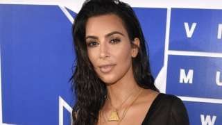 Image copyright                  AP                  Image caption                                      Kim Kardashian West was robbed by armed men dressed as police officers in Paris last week                                US reality TV star Kim Kardashian West is suing a celebrity gossip website for claiming that she faked being the victim of a robbery in Par