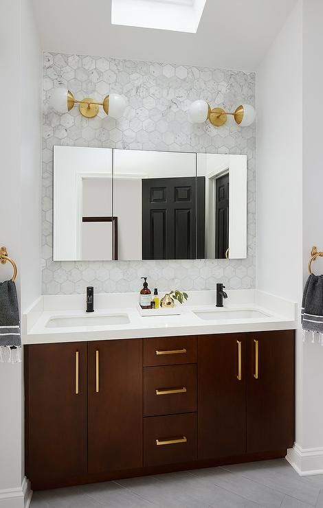 Under a skylight, gray wood like floor tiles lead to a brown dual washstand accented with Schoolhouse Electric Edgecliff Pulls and topped with a white quartz countertop contrasted with oil rubbed bronze faucets positioned beneath frameless medicine cabinets fixed to large marble hex backsplash tiles beneath Cedar & Moss Theo Sconces.