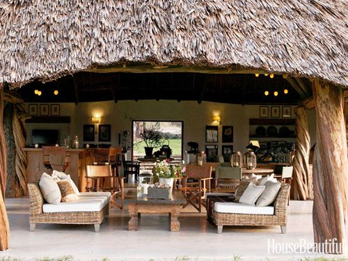 In an open-air house in Kenya decorated by Suzanne Kasler, sinewy columns cut from fallen trees at Maralal flank South of Market outdoor sofas.