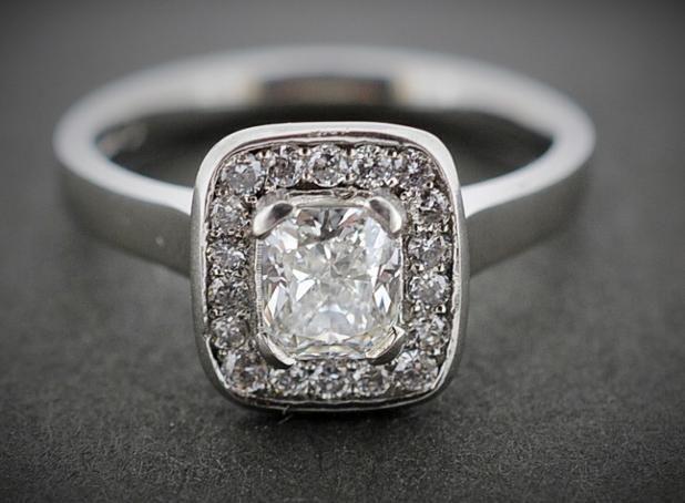 A 0.70ct cushion cut diamond set in a platinum and diamond halo. Principle diamond (0.70ct) has a GIA diamond certificate. G colour, VS2 clarity #Engagement #Diamonds #PlatinumCork