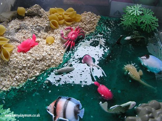 Ocean World - Sensory/Food Tray  Lime Jelly  Blue Food Colouring  Water  Porridge Oats  Homemade Chocolate Play Dough  Shell Pasta Shapes  Selection of different sea creatures