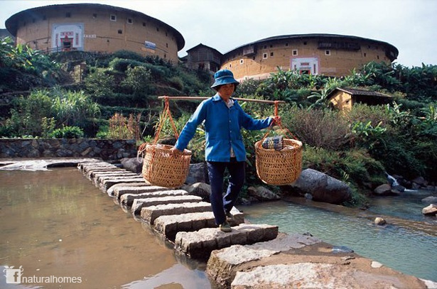 These are Tulou, built by the Hakka people of China. The Tulou are massive rectangular (representing Earth) or circular (representing Heaven) fortress walls of rammed earth several metres thick. These buildings have survived since the 17th century demonstrating the durability of rammed earthen structures. More, including video, on www.naturalhomes.org