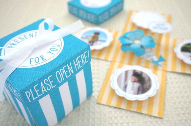 誕生日やいろいろなお祝いの時に、ひと言気持ちをしたためてメッセージカードを贈ると、とても喜ばれますよね。そのメッセージカードに、びっくり箱みたいな仕掛けをほどこして「驚き」と「笑顔」も一緒にプレゼントすることができる素敵なメッセージカードが、実はSNSでじわじわと人気が出てきているんです。  もともとは韓国のカップルが始めたとかと言われているプレゼントBOXの形をした立体のメッセージカードで、「エクスプローディングボックス」とか「サプライズボックス」と言われています。 箱のフタをあけると、パタッと箱が開き、素敵にデコレーションされた思い出の写真やメッセージが目に飛び込んでくるんです。  自分で作るとなると、楽しそうだけど準備がちょっと大変。 思い出の写真の他に、カードの材料となる厚紙や、かわいい色紙、シール、マステなどの準備が必要になるし、デザインもどんなものにしようかと一から自分で考えるとなると、なかなか大変。  「作ってみたいけど、ちょっとハードルが高いなぁ…」 なんて心配はいりません。 実は、そんなエクスプローディングボックスが簡単にできちゃうキットがあるんです!…