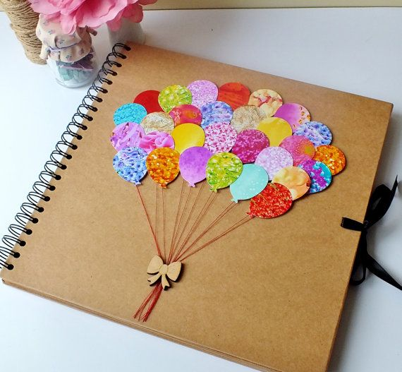 Beautifully hand-decorated scrapbook album - makes a perfect baby album / scrapbooking, photo album and even wedding comments book. The cover is so colourful, displaying 28 beautiful bright balloons, real cotton thread and a gorgeous wooden bow.  This lovely book has a high quality hardboard front and back, with 40 sheets of heavyweight 200gsm kraft card, providing 80 pages! Perfect for your scrapbooking, or just add some photo-corners to use as a fabulous photo album!  Your album can a...