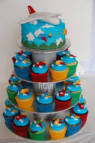 Plane shaped cake on top, tiers of cupcakes with frosting and clouds, with the chocolate plans on top. @Becca Paro