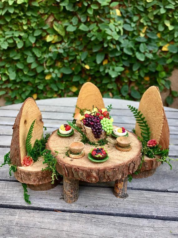 This enchanting woodland fairy table is set with miniature pastries, acorn bowls and a gorgeous fruit centerpiece. The tiny pastries and fruit display are amazingly detailed and just beautiful. Each pastry is resting on a green ceramic plate and all items are glued down. The table #miniaturefairygardens #fairyfurniture