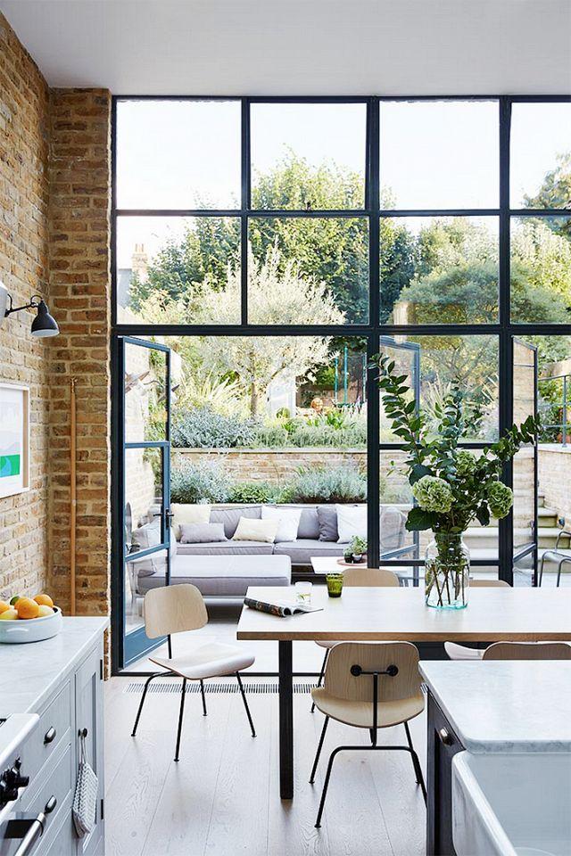 An indoor-outdoor dining space with large windows, exposed brick and wood floors