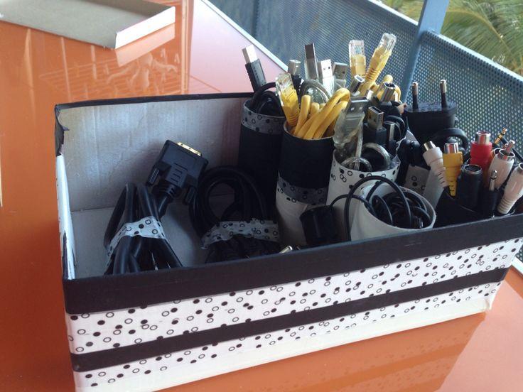 Rangement pour câble avec une boîte à chaussures et des rouleaux de papier toilettes.