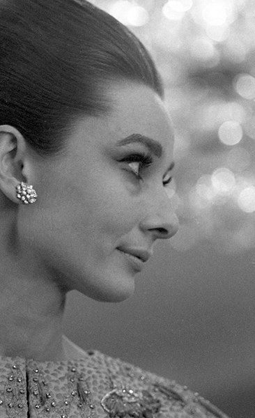 """The actress Audrey Hepburn photographed by Angela Williams in her suite at the Hôtel Ritz, located at Place Vendôme, in the 1er arrondissement of Paris (France), before the French premiere of her new movie """"My Fair Lady"""", held at the Théâtre du Châtelet, on December 22, 1964."""