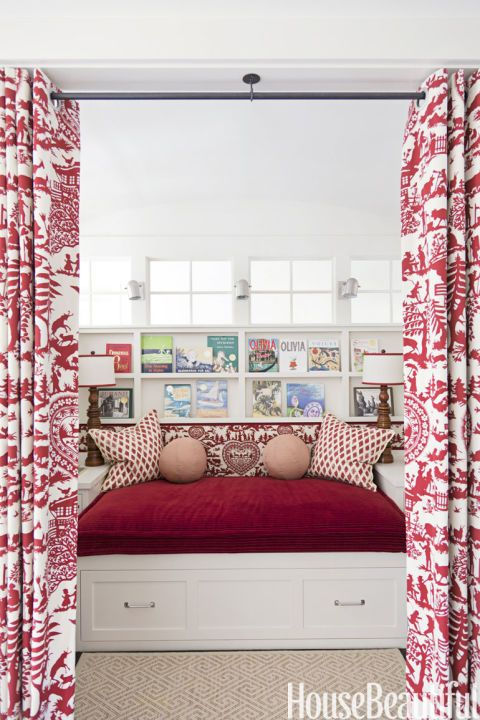 """A built-in bed and curtains create a private, magical room at the top of a staircase. """"This cozy nook is the children's reading room,"""" Ann Wolf says, """"and it doubles as a backstage when they're doing theatrical plays. It's a space for the imagination. They adore it. It's every kid's fantasy — mine, too."""""""