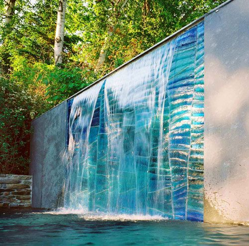 Cascade, the sculpture above by SWON Design, is a cast glass wall situated in a landscaped garden setting on the shores of Lake Ontario in Toronto. It measure 7′ high by 10′ long. The cast glass wall is made up of 77 ladle poured glass blocks in varying tones of aqua blue/green with texture simulating flowing water. The cast glass wall incorporates a water feature that allows for a controlled spill over the glass.