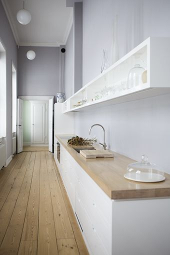 Shotgun Galley Kitchen = Open storage, wooden counter tops, white cabinets, spherical pendant lamps. Change the light lavender to a more bluish tone and I think this would be perfect.