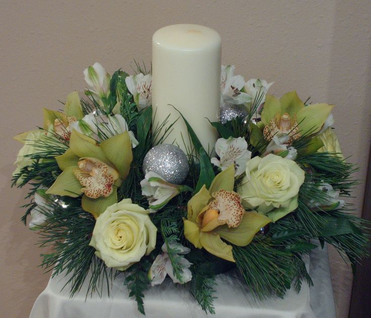 Holiday Centerpieces using green orchids, green roses, and silver and white accents