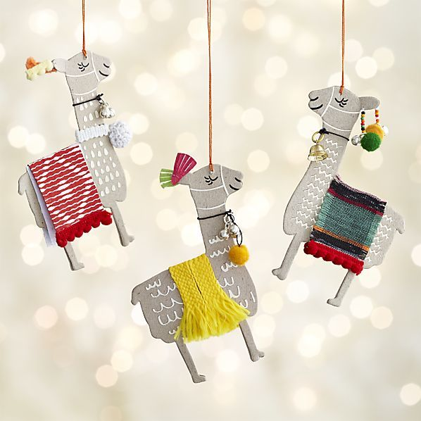 Whimsical llama Christmas ornaments are handcrafted with handmade paper, accented with brightly colored fabric blankest, bells and pompoms.