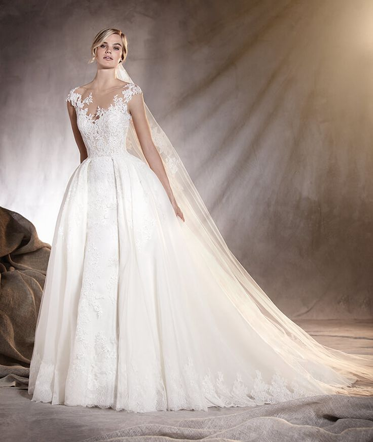 Call the boutique to see this stunner named Adela - Wedding dress in tulle and lace with a low plunge on the back by @pronovias! #illusionlace #lowback