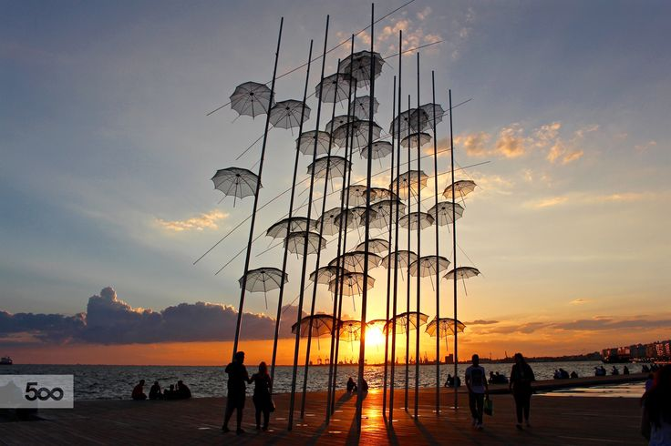 Sunset behind the umbrellas sculpture at the waterfront of Thessaloniki, Greece.