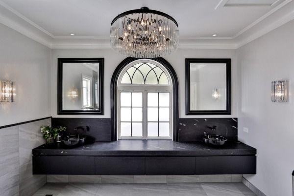 Black frames the mirrors, arched window and chandelier in this spacious bathroom designed by Leonie Von Sturmer of Von ...