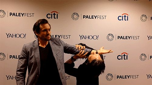 Mads Mikkelsen attempting to eat Hugh Dancy's arm.