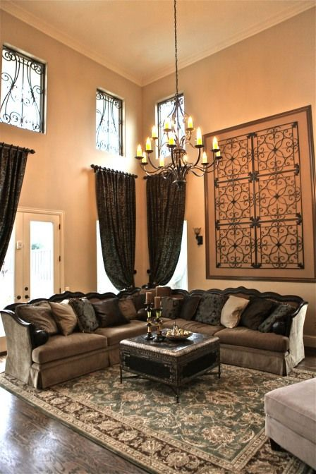 Custom window treatments on tall walls combined with faux iron