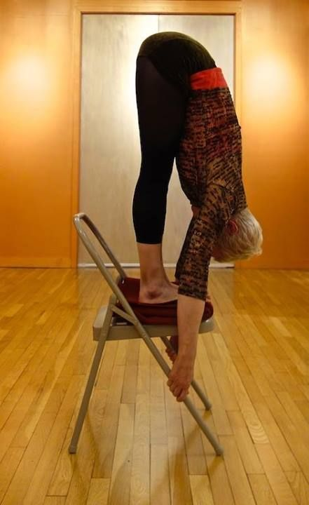 Uttanasana, using the chair for greater spinal extension. Iyengar method.