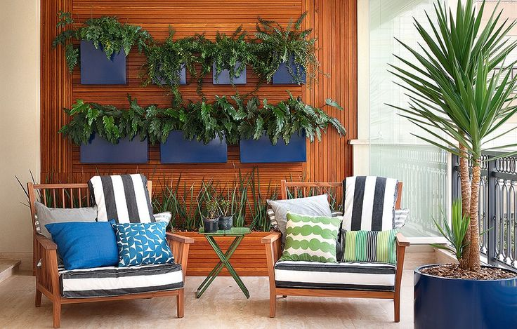 A moradora queria uma parede inteira de plantas, mas buscava um jardim que exigisse pouca manutenção. A solução criada pela paisagista Claudia Diamant foi um grande e charmoso painel feito com diferentes larguras de madeira cumaru, que acomoda uma jardineira e sete cachepôs de aço, pintados de azul