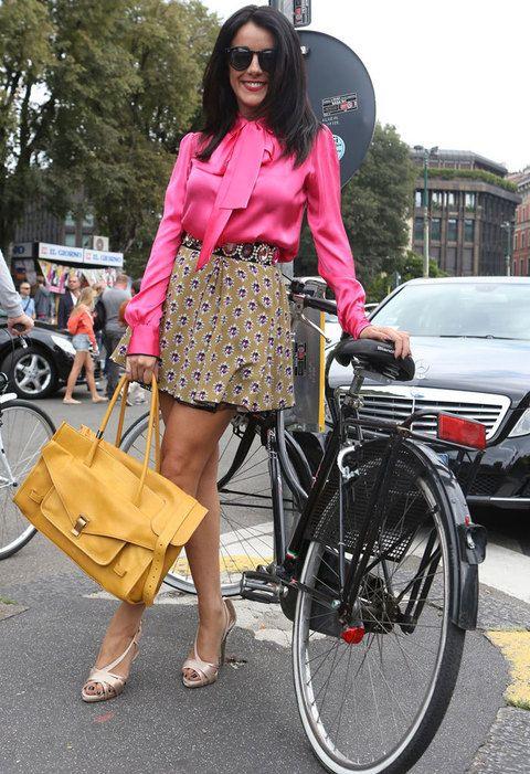 Camisa fucsia de corte muy lady con un lazo al cuello, falda de vuelo estampada con cinturón joya y maxi bolso color camel.