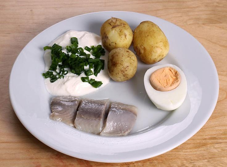 Traditional pickled herring with sourcream and chopped chives, steamed potatoes and egg, served for the midsummer holiday.  Inlagd sill, gräddfil med hackad gräslök, potatis och en ägghalva serverat för midsommar.