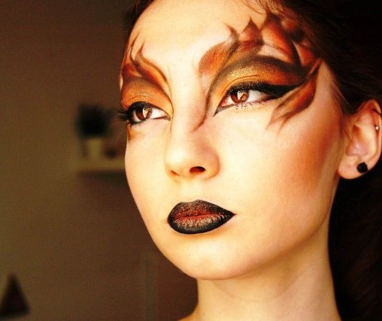 """A dramatic cut crease has never looked so amazing! If this look is something you covet then begin by creating a black cut crease with Makeup Geek's Corrupt extending it past the inner corner onto the nose and past the eye to the temple. Use the same black to draw your """"flames"""" above the cut crease and from the temple extending down past the outer corner of the eye. Fill in each one using your favorite oranges, reds and browns. Remember, the key to a look like this is shading and blending…"""