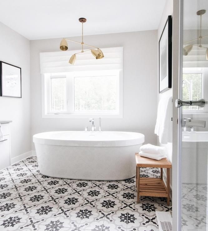 An antique brass modular shade chandelier hangs over an oval soaking bathtub fitted with a polished nickel floor mount tub filler and placed on white, gray, and black mosaic floor tiles beneath a window.
