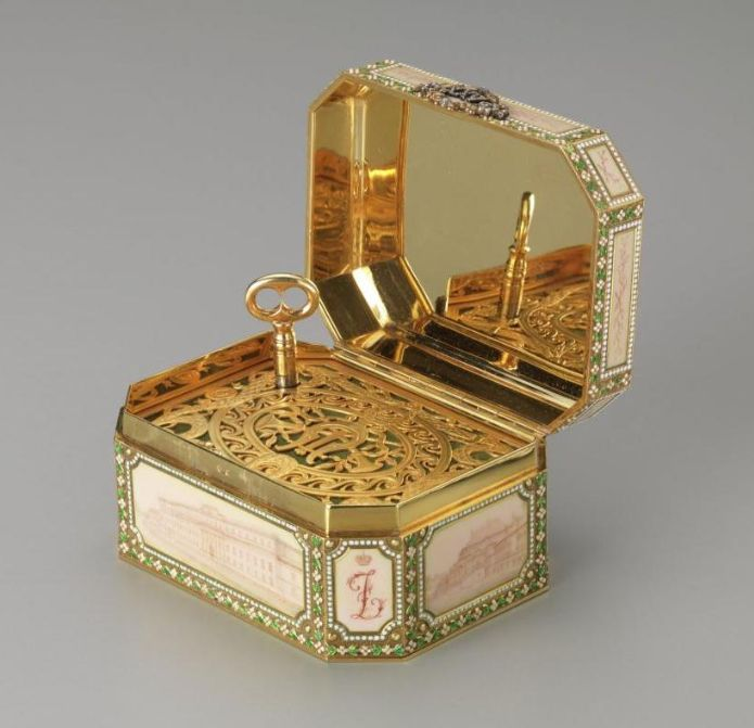 "In 1907 Felix and Nikolai Iusupov gave this Fabergé music box to their parents, Prince Felix and Princess Zenaida, as a twenty-fifth wedding anniversary present. Six of the Iusupov palaces are depicted in sepia enamel panels. When opened, the music box plays ""The White Lady"" by François Boieldieu, the march of the senior Prince Felix's regiment, the Imperial Horse Guards."