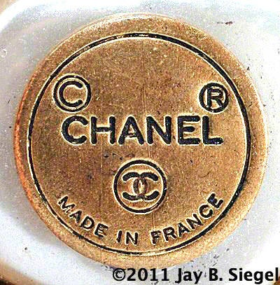 """Chanel Round Mark - 1970s- Photo by Jay B. SiegelThis is one of several similar marks used by the House of Chanel in the 1970s moving into the early 1980s. It shows the copyright and registered symbols above CHANEL in block letters on a round cartouche. Below that is the familiar interlocking CC logo and """"Made in France."""" Marks from this era can be found both with and without the circular outline shown here."""