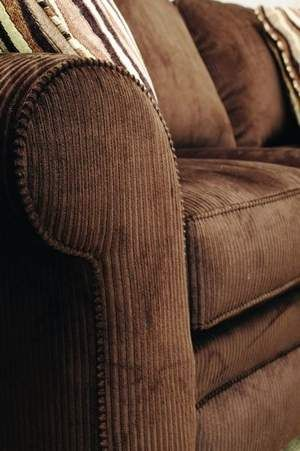 A chocolate brown, wide-wale corduroy sofa has three semi ...