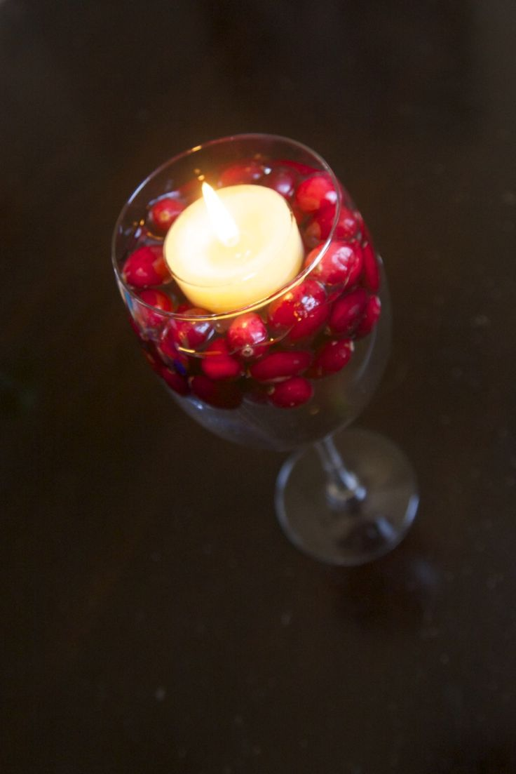 Wedding decorations - wine glass with water, floating cranberries and floating candle.