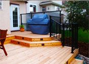 CREATE ESCAPE - Discovery Ridge.  Two tiered deck that incorporates a BBQ area and lower table for entertaining. Black aluminum railing and step lighting.