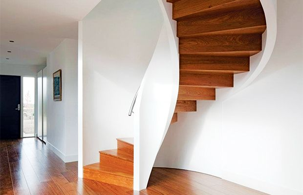 Helical staircase with hidden mild steel carcass clad in iroko, with stainless-steel handrail and painted timber board, from £42,000, EeStairs
