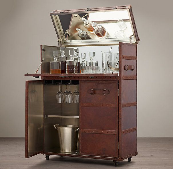 "RESTORATION HARDWARE MAYFAIR BAR CART - VINTAGE CIGAR $2695 Like the stalwart trunks that accompanied travelers by sea and rail a century ago, our bar cabinet is solidly built, clad in leather and edged all around with scores of brass nailheads hammered by hand. The lower doors open to a roomy interior, lined with stainless steel and fitted with a shelf for bottles and barware. The hinged top lifts and the front panel drops down. 36""W x 16½""D x 50""H; 187 lbs."