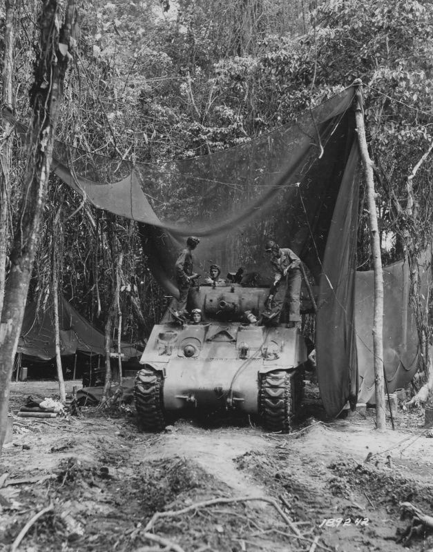 Crew American medium tank M4 'Sherman' loads ammunition in the car in the jungles of Bougainville (Bougainville). Stretched over the machine camouflage net.