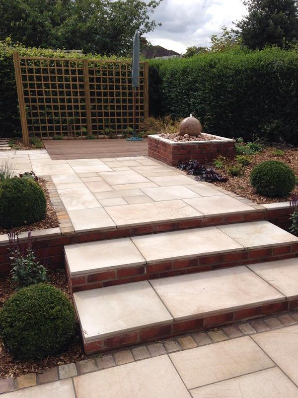 After photo - new steps integrate the two levels & lead the eye to the water feature. Paving is Marshall's sawn sandstone in 'caramel cream'