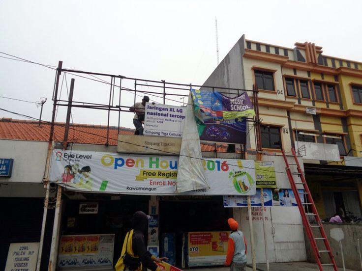 Petugas UPPD Pulo Gadung membongkar spanduk dan papan reklame di atas toko warga