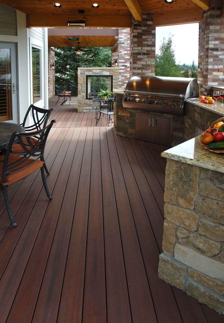 This deck is ready for entertaining with its #outdoorkitchen and #outdoorfireplace. The deck is low-maintenance composite decking from Fiberon