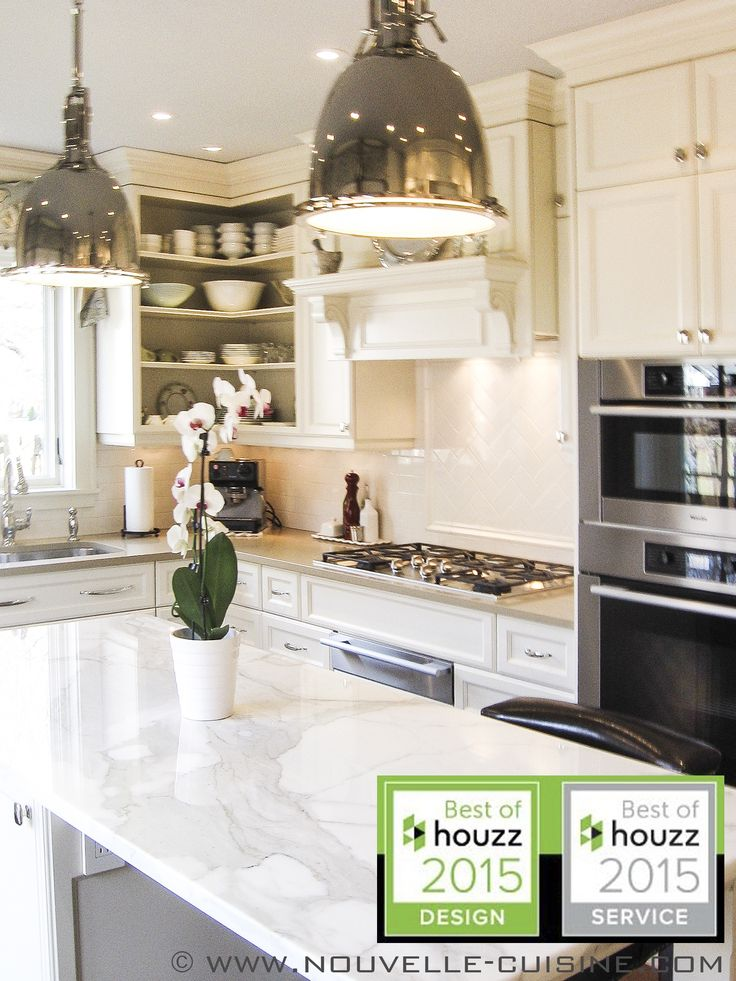 A classic kitchen with cream lacquered wood cabinets, topped with quartz and granit counters. / Une cuisine classique avec des armoires en bois laqué couleur crème, surmontées de comptoirs en quartz et en granit.