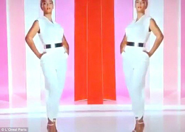 Strike a pose: The singer wears a white belted jumpsuit as one point as she appears in front of a colourful background